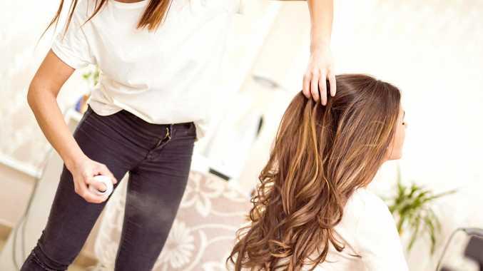 Hairdresser spraying a customer's hair.