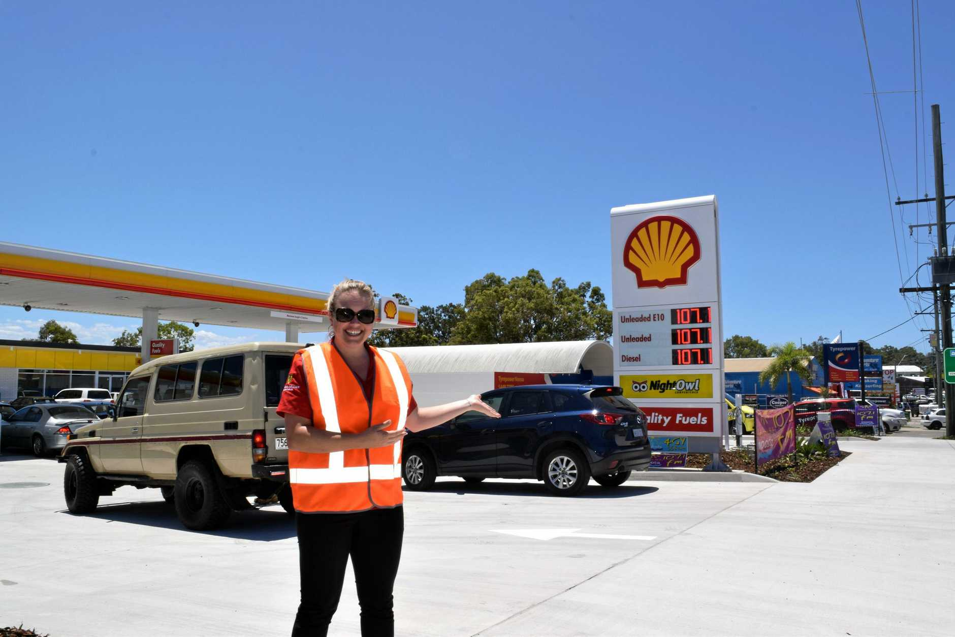 PRICE IS RIGHT: An employee at the new Noosaville Shell and NightOwl Service station points to the cheap fuel deal on Thursday.