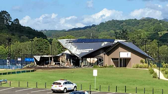 Emergency services inspect the scene after an early morning fire gutted the Terranora Tennis Centre.