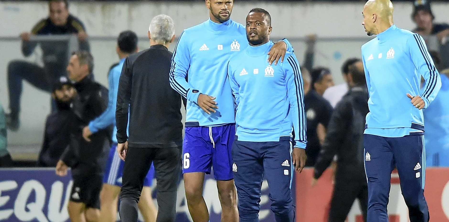 Marseille's Patrice Evra, second from right, is led away by his teammate Rolando after a scuffle with Marseille supporters.