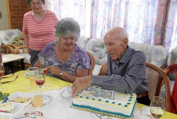 Ronald Ramage cuts the cake for his 100th birthday at Crows Nest, with his wife Judith.