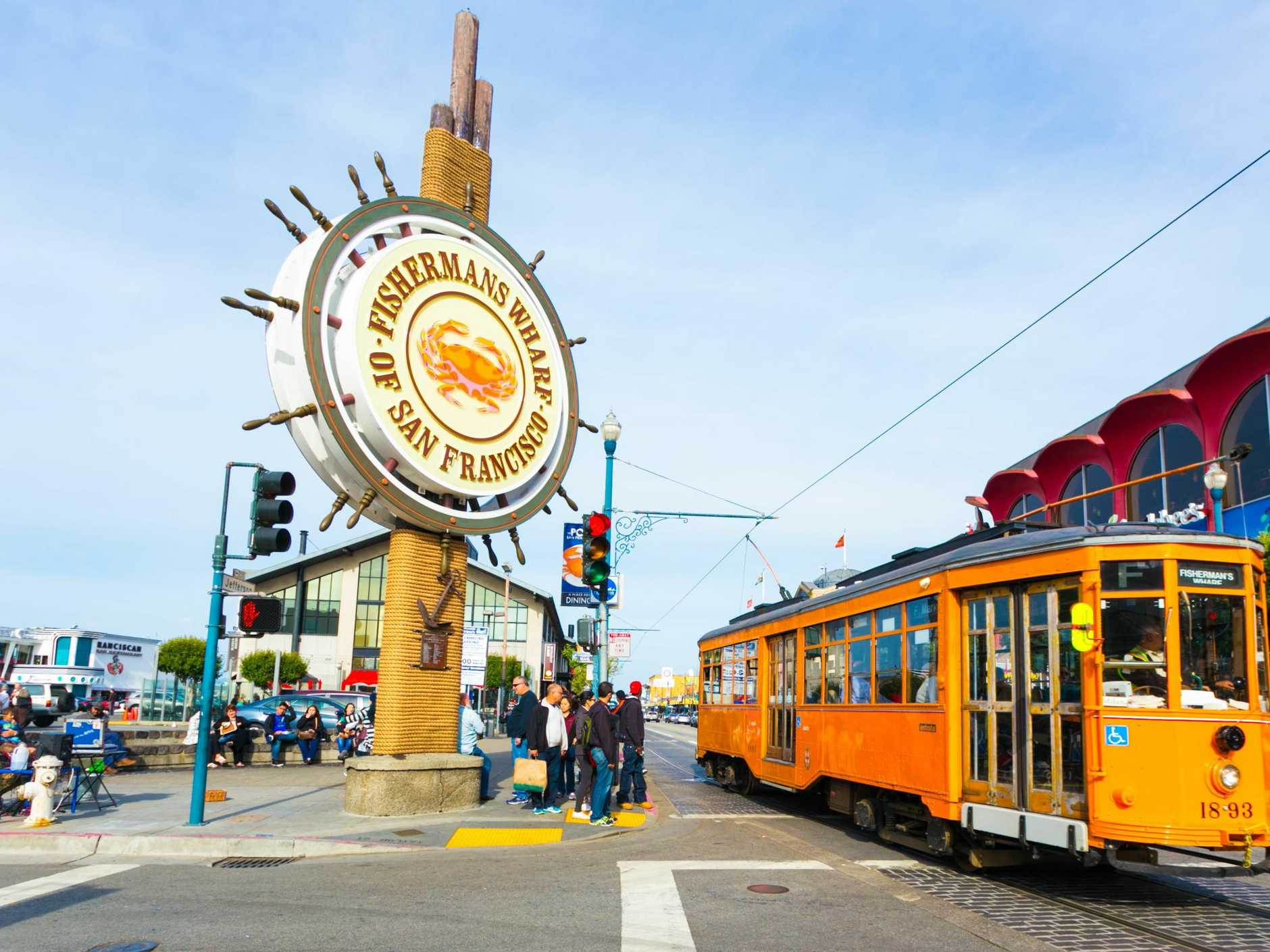 San Francisco, United States - May 5, 2016: Orange vintage Swiss F Market streetcar rolls by large sign at entrance to the tourist attraction of Fisherman's Wharf on the corner of Beach and Jones Street. Horizontal