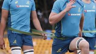 New Wallabies player Matt Philip (2nd left) stretches during a training session at Leichhardt Oval.