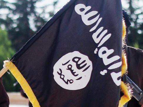 Islamic State of Iraq and the Levant propaganda photo showing masked militants holding the ISIS black banner.
