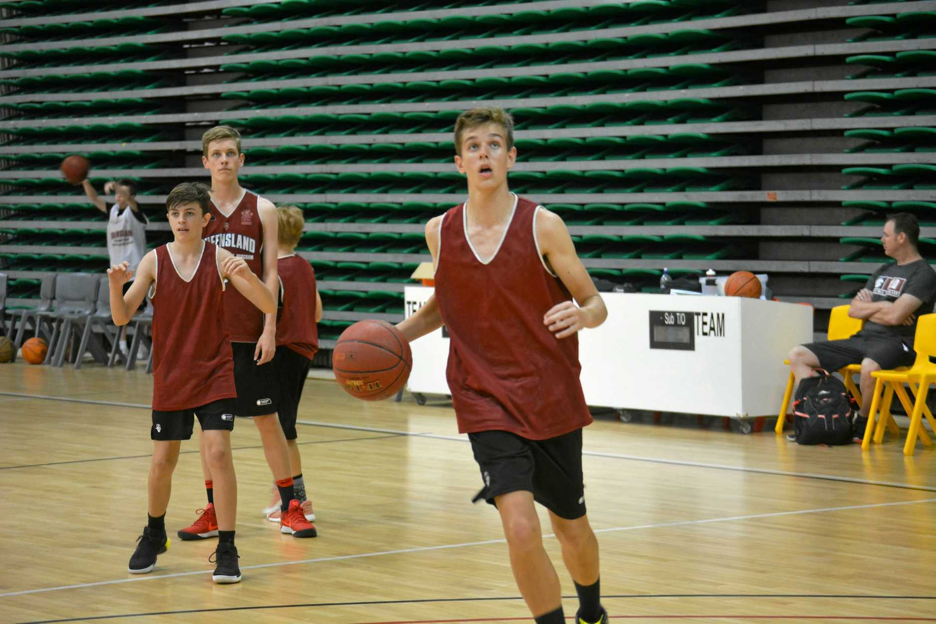 Marley Evans drives at the basket with Seth Collins and Jack Small looking on.