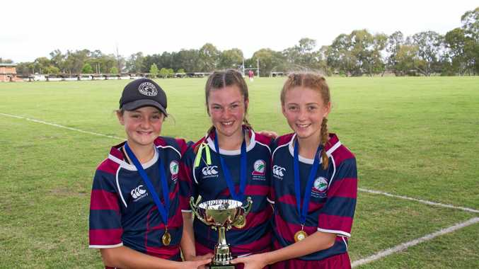 WINNING FEELING: Mary MacKillop students (from left) Zoe Wallace, Holly Anlezark and Jessica Wallace celebrate their Rugby 7s victory at Scots PGC College.
