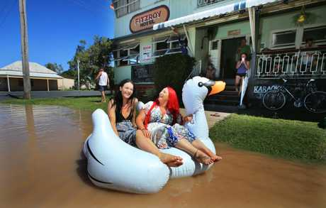 Tahlia Thomasson, 19, and Fitzroy Hotel publican Tiona McGuigan fool around in floodwater on a pool toy in front of the hotel.