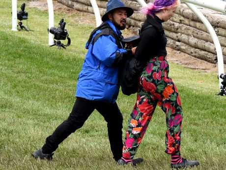 A female protester is removed after trying to run down the straight. Picture: Nicole Garmston