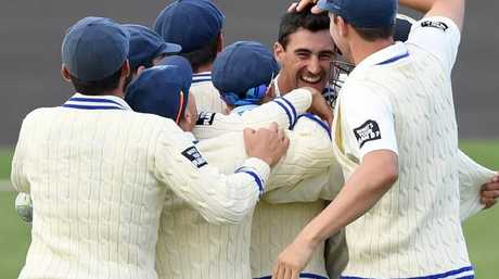 Blues players mob Starc after his second hat-trick.