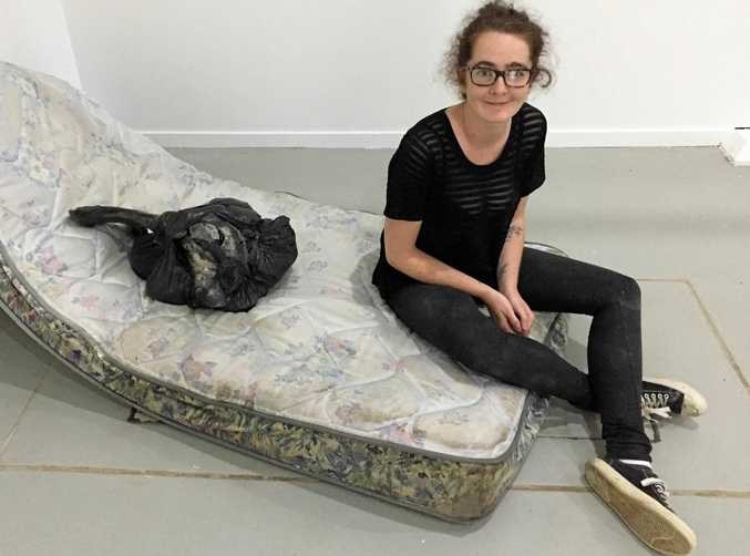 SUFFERING FOR ART: Jessica O'Connor sits beside part of her installation, Survival of the Fittest, at the Southern Cross University 2017 Visual Arts Graduate Exhibition.