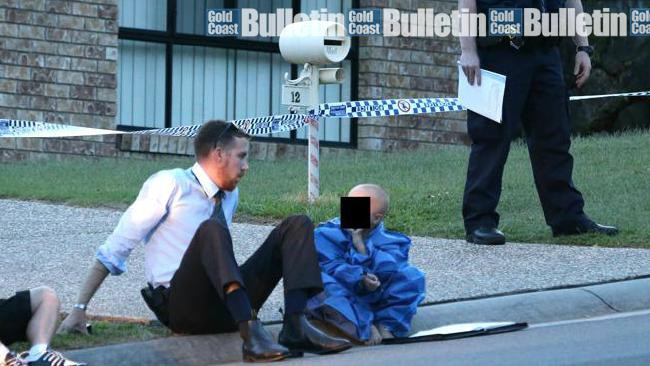 A young boy is comforted at the scene of an Upper Coomera double murder. Photo: Glenn Hampson