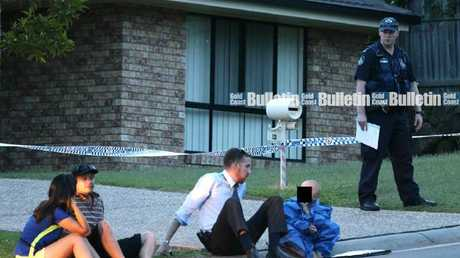A five-year-old boy, dressed in a forensic suit, sits in the gutter with a detective after reportedly witnessing his parents' double murder at Upper Coomera. Pic: Glenn Hampson