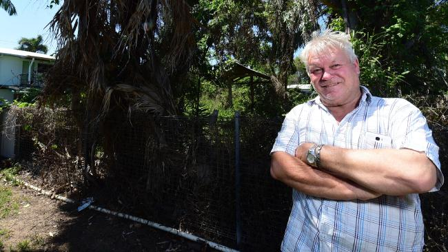Kelso resident Philip Wood stands by the fence where is neighbor's yard is overrun. Picture: Evan Morgan