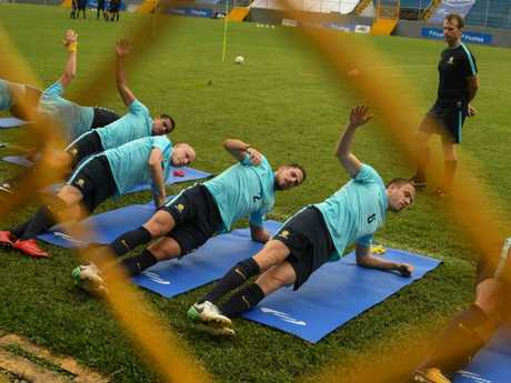 The Socceroos warm up before their first training session.