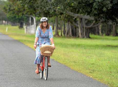 Amanda Goodwin (winner of the inaugural Lorna McDonald Essay Prize) cycling along Port Curtis Road near Woolwash Lagoon which was the subject of her writing.