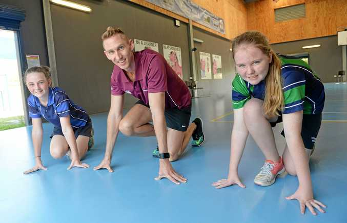 Victoria Park State School students Imogen Wood and Danika Arvidson with sprinter and Commonwealth Games hopeful Craig Burns during his visit to Mackay this week.