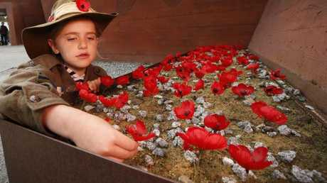 Grace, 8, wears a traditional poppy on her hat as she plants a poppy at the Shrine of Remembrance.