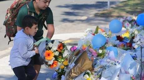 Children lay flowers at the memorial outside the Sydney school.