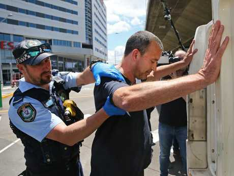 Pictured arriving fro New Zealand at Sydney International Airport is conman, Dan Albert as he is escorted by police to a waiting police vehicle. Picture: Richard Dobson
