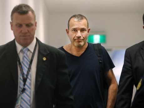 Pictured arriving fro New Zealand at Sydney International Airport is Sydney conman, Dan Albert as he is escorted by police to a waiting police vehicle. Picture: Richard Dobson