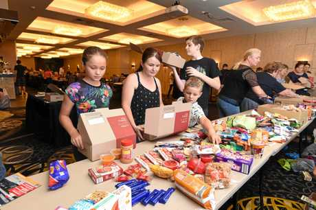 Care packages - (L) Annika,9, Bonnie and Zander,6, Genrich and Michael Buckley filling care packages for our troops serving overseas at Christmas.