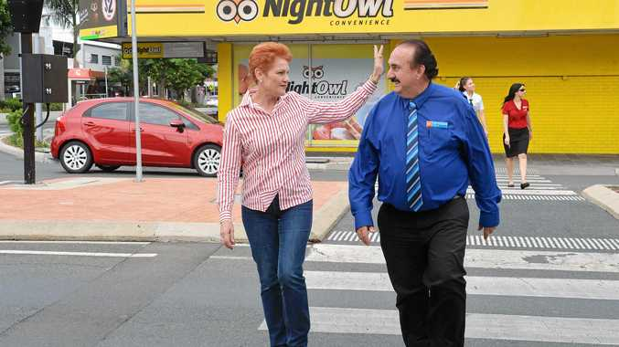 One Nation's Pauline Hanson waves to people while walking along Victoria Street with Mackay's One Nation candidate Jeff Keioske.
