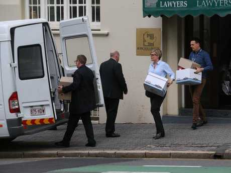 Items are removed from the Bosscher Lawyers offices during last year's police raids.