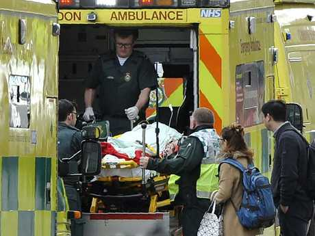 Paramedics load a victim into the back of an ambulance as members of the emergency services work on Westminster Bridge. Picture: AFP