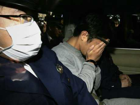 Takahiro Shiraishi covers his face under arrest after police found the decaying remains of nine people in his Tokyo flat. Picture: AFP.