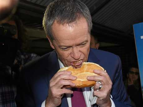 Leader of the Opposition Bill Shorten eats a sausage sandwich from the side.