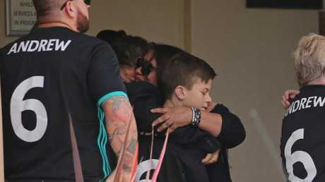 The brother of Andrew Encinas is consoled by a family friend at the funeral. Picture: Richard Dobson