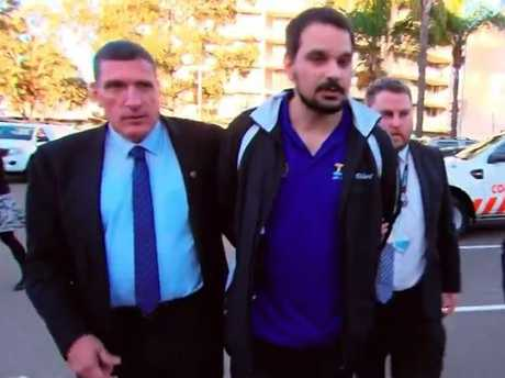 Richard Palmer is led away by detectives in the Parramatta McDonald's car park. Picture: Channel 7