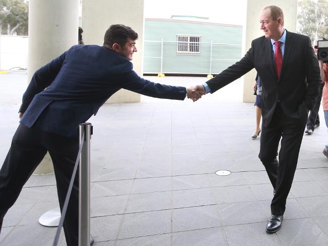 Labor Senator Sam Dastyari shakes hands with Fraser Anning as he arrives at Parliament House in Canberra today. Picture Kym Smith