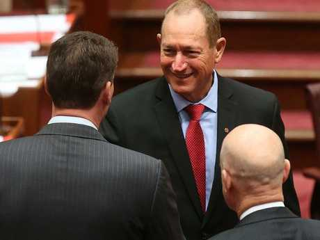 New Senator Fraser Anning after being sworn in shaking hands with Senator Cory Bernardi and Senator David Leyonhjelm in the Senate Chamber, Parliament House in Canberra. Picture Kym Smith