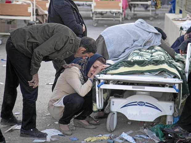 Relatives weep over the body of an earthquake victim in Sarpol-e-Zahab, western Iran, following Monday's earthquake.