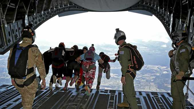 TIME TO FLY: Female skydivers from the Women in Adventure Sports program jump out of a No 36 Squadron C-17A Globemaster aircraft above RAAF Base Amberley. (inset) Group Captain Adam Williams with Brisbane Legacy Youth Ambassador Brianna Anderson.