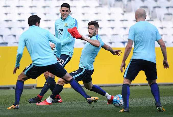 Australia's Tom Rogic (2nd left) laughs as he passes the ball during a training session at Stadium Australia in Sydney, Tuesday, November 14, 2017. The Australia 'Socceroos' play Honduras on Wednesday night in a second leg Russia 2018 World Cup playoff football match. (AAP Image/David Moir)