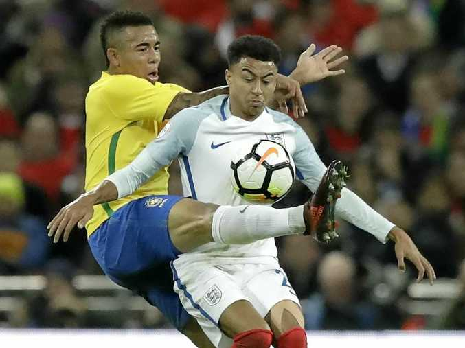 Brazil's Gabriel Jesus, left, and England's Jesse Lingard challenge for the ball.