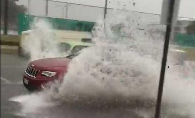 A car drives through flash flooding in Cotton Tree.