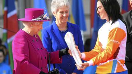 Retired cyclist Anna Mears from Australia, right, receives the Commonwealth Games relay baton from Britain's Queen Elizabeth II, right,  at the launch of the relay at Buckingham Palace in  London Monday March 13, 2017.  The XXI Commonwealth Games are  being held on the Gold Coast in Australia in 2018. (Toby Melville/Pool Via AP)