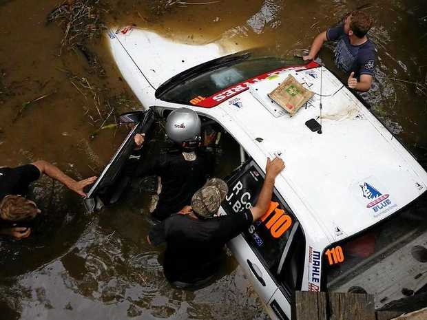 The image posted on Twitter of Kennards Hire Rally Australia spectators rushing to the assistance of Ross Cox and co-driver Janet Binns after their went into a creek off Rhones Creek Rd near Talarm hall.