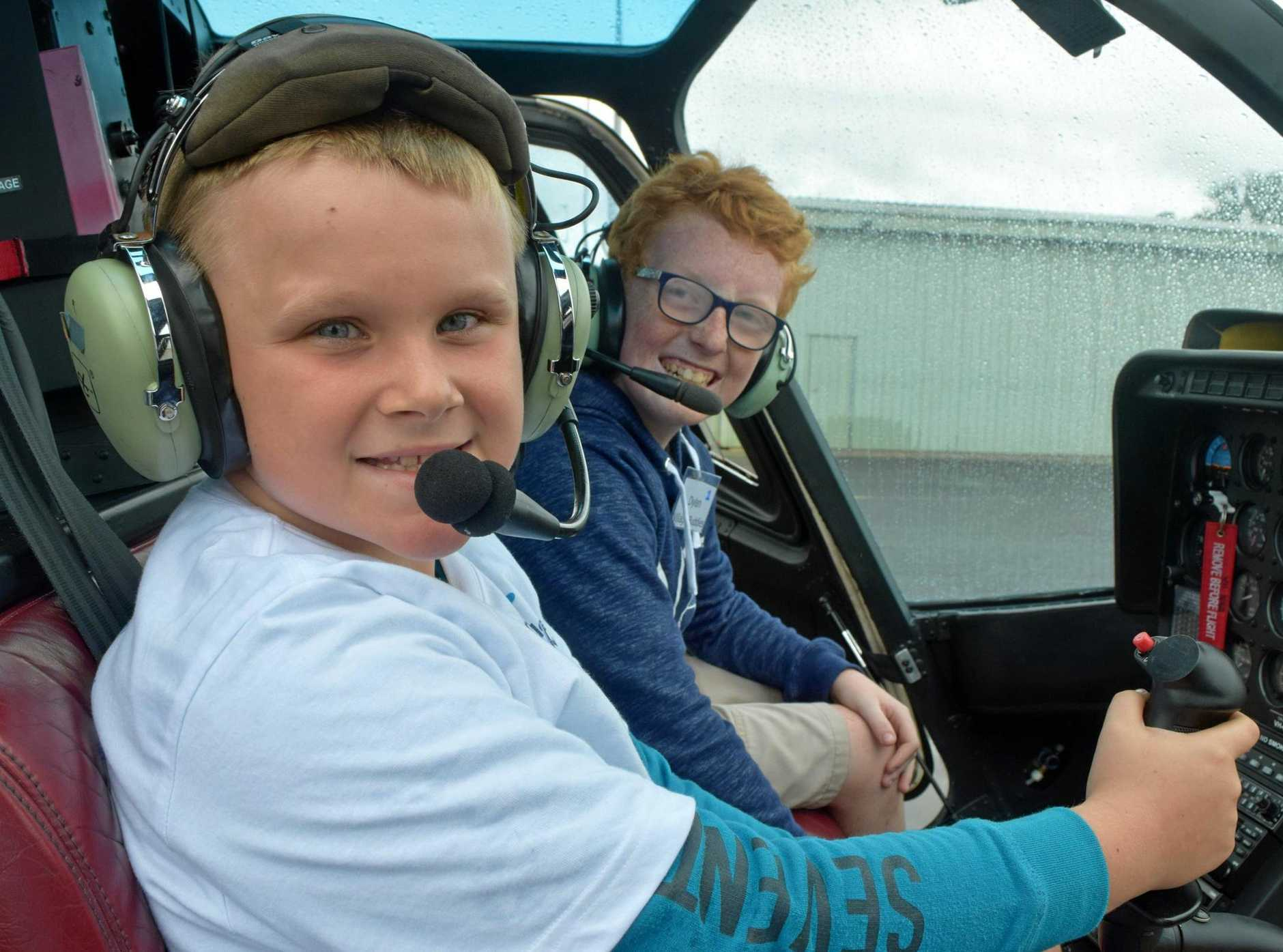 Casey Thompson (left) and Dylan Dinicco take control of a chopper at Becker Helicopters flight Academy.