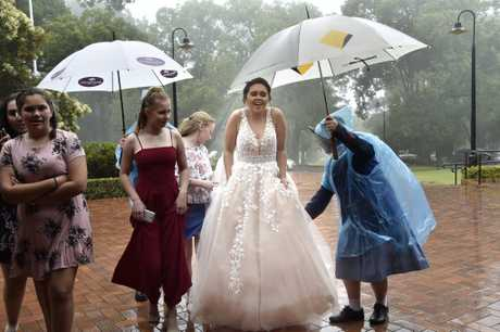 It was all hands on deck to ensure year 12 graduates arriving for the valedictory mass were kept dry. Cheyenne Crombie makes her way to the Graham Centre. November 2017