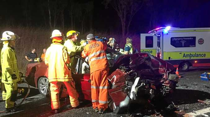 STUCK: Queensland emergency services personnel work to cut free a driver from a car following a head-on crash on the Bruce Highway north of Rockhampton.