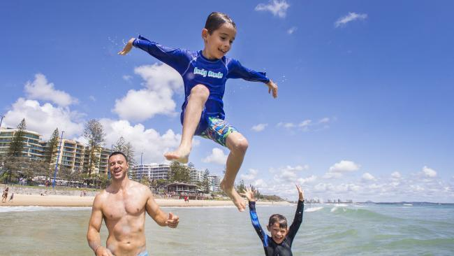 Dad Mark Que from Gladstone goes topless by sons Jordie, 7, and Cooper, 9, are well protected, at Mooloolaba. Pictured: Lachie Millard