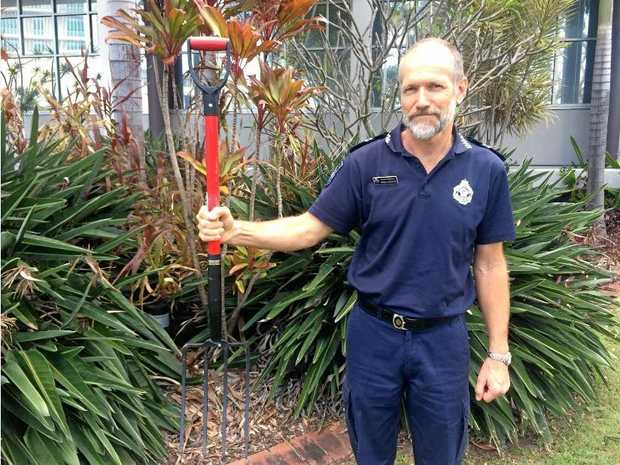 Maroochydore police officer Senior Constable Jeremy Spencer holds the red pitchfork police say was used in an attempted armed robbery at Palmwoods.
