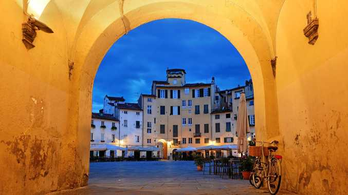 ENCHANTING: The arch entrance of Piazza dell'Anfiteatro in Lucca, Italy at night.