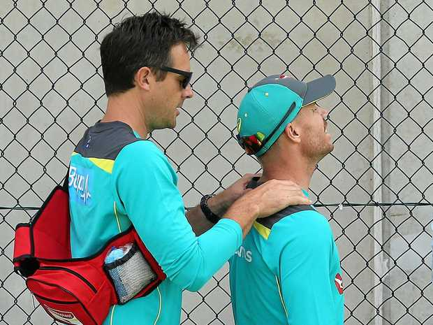 David Warner (right) has his neck looked at by medical staff.