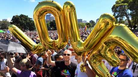Supporters of same-sex marriage gather to celebrate the announcement in a Sydney park. Picture: AFP PHOTO / WILLIAM WEST