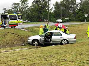 Firies free woman from crash wreckage at major roundabout